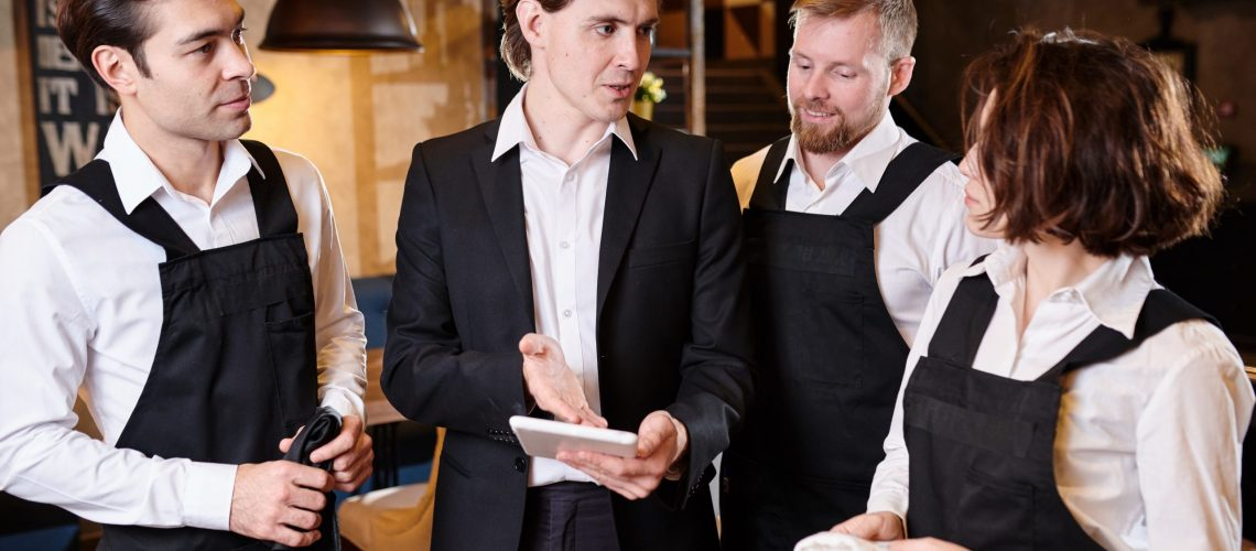 Content confident handsome young manager pointing at tablet screen while assessing work of waiters and explaining their mistakes